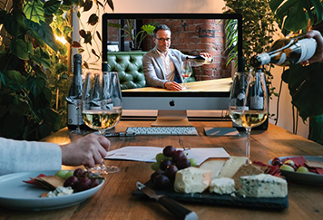 a video of a man on the screen and guests pouring wine
