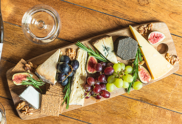 a selection of wine and cheese on a table